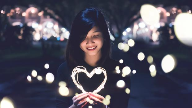 smiling woman of asian descent, holding a light ring in the shape of a heart
