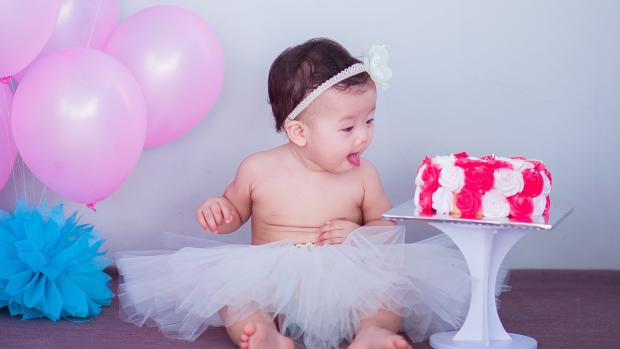 baby looking at a cake